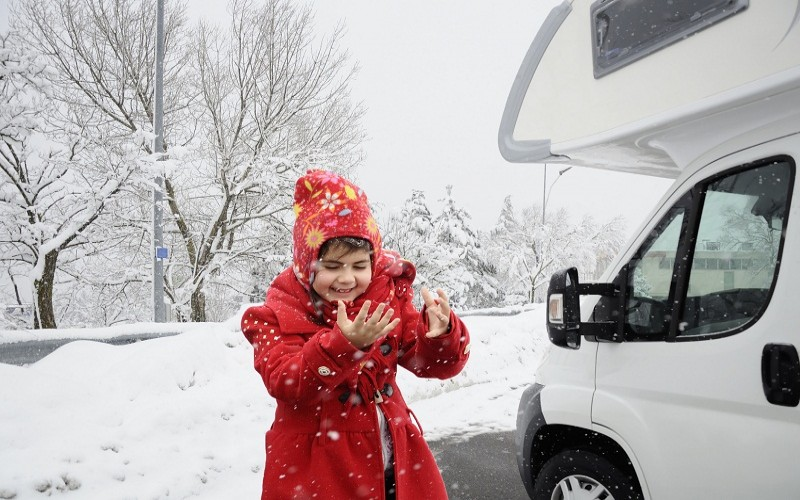 Child in snowfall by RV