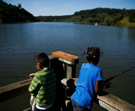 Eight-year-old Marco David (left) and 7-year-old Marietou Keita fish on the docks at Lake Chabot [Photo Credit: Mason Trinca]
